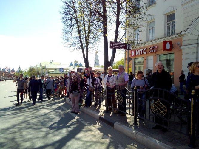 Люди, которые стоят на тротуаре. Их не меньше, чем в колонне