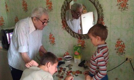 дедушка показывает правнукам свои медали